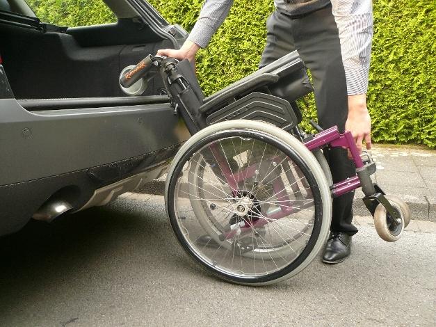 Rollstuhl am RollirolleR und einem festen Rahmenteil greifen und auf die ROlle des RollirolleR kippen