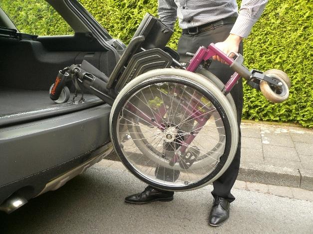 Rollstuhl in den Kofferraum rollen. D.h. die Räder des Rollstuhls liegen an der Stoßstange an und die Rolle des RollirolleR rollt auf dem Boden des Kofferraums